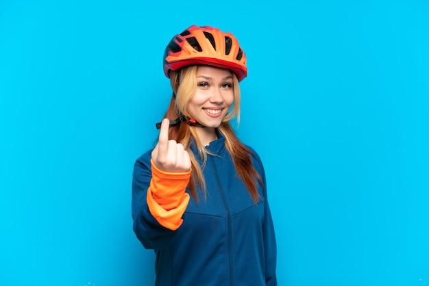 Jong wielrennermeisje dat op blauwe achtergrond wordt geïsoleerd die komend gebaar doet