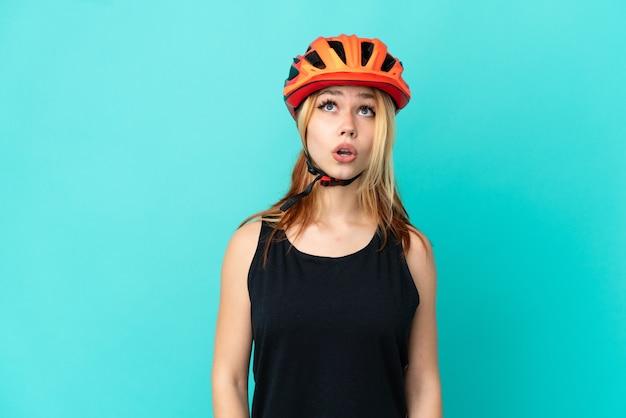 Jong wielrennermeisje dat over geïsoleerde blauwe achtergrond omhoog kijkt en met verbaasde uitdrukking