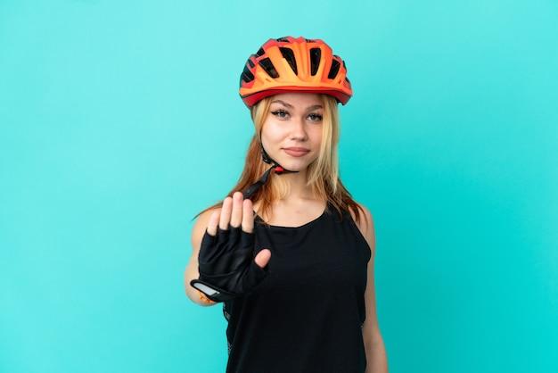 Jong wielrennermeisje dat over geïsoleerde blauwe achtergrond stopgebaar maakt