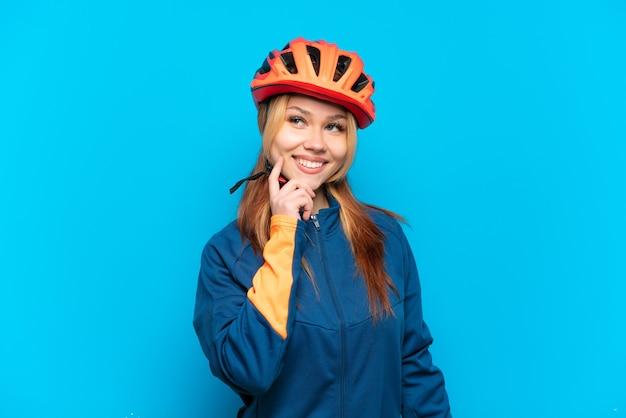 Jong wielrennermeisje geïsoleerd denkend aan een idee terwijl ze omhoog keek