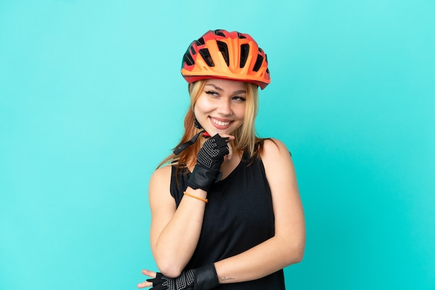 Jong wielrennermeisje over geïsoleerde blauwe achtergrond die aan de kant kijkt en glimlacht