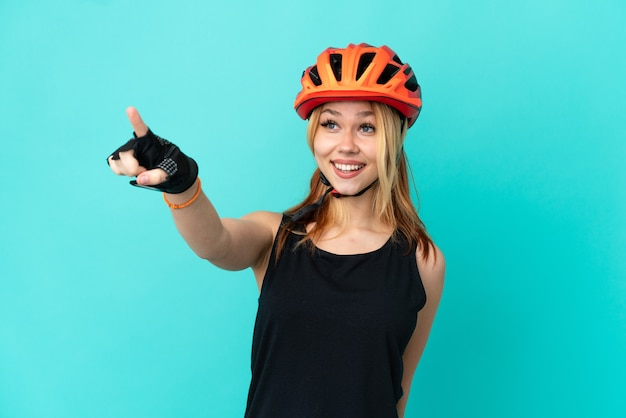 Jong wielrennermeisje over geïsoleerde blauwe achtergrond die weg wijst
