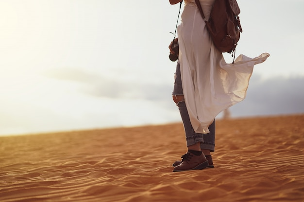 Jong wijfje dat de woestijn, het zandige strand met zak en camera onderzoekt.