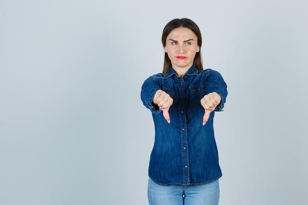 Jong wijfje dat duimen neer in denimoverhemd en jeans toont en ontevreden kijkt