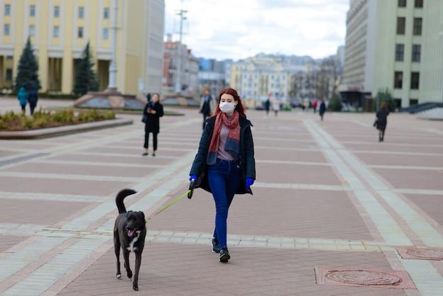 Jong wijfje dat een gezichtsmasker gebruikt dat met haar hond loopt.