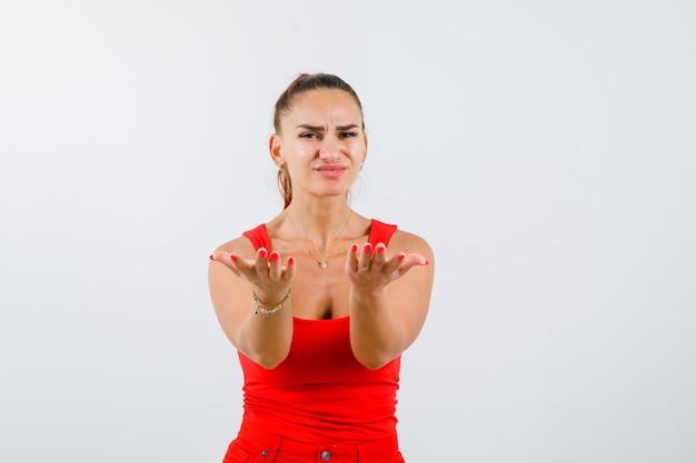 Jong wijfje dat gebaar in rood mouwloos onderhemd, broek toont en leuk, vooraanzicht kijkt.
