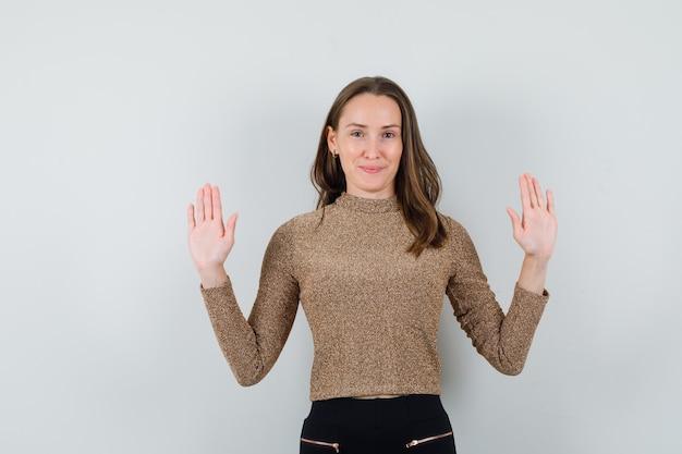 Jong wijfje dat haar handen opheft terwijl zij haar handpalmen in gouden blouse toont en kalm kijkt. vooraanzicht.