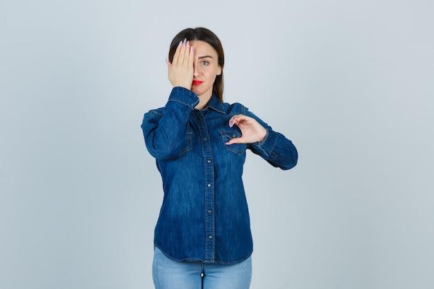 Jong wijfje dat half hartgebaar vormt terwijl hand op oog in denimoverhemd en spijkerbroek wordt gehouden en er mooi uitziet