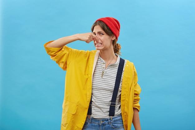Jong wijfje dat hand op neus houdt die walgelijk kijkt terwijl zij iets onaangenaams ruikt dat over blauwe muur wordt geïsoleerd. ontevreden vrouw toont haar reactie op stinkende geur uit de keuken