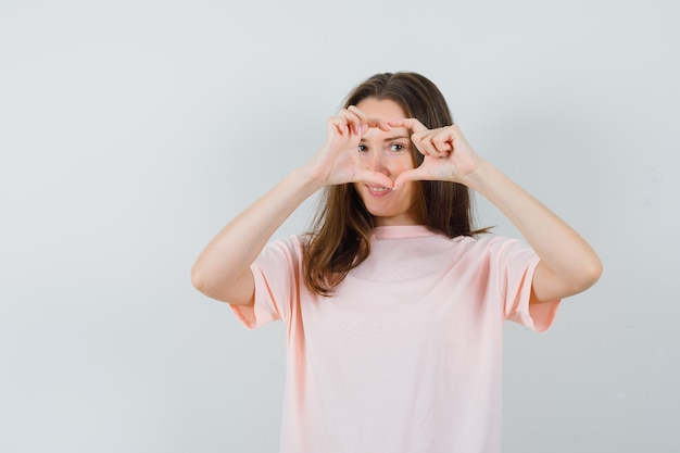 Jong wijfje dat hartgebaar in roze t-shirt toont en leuk, vooraanzicht kijkt.