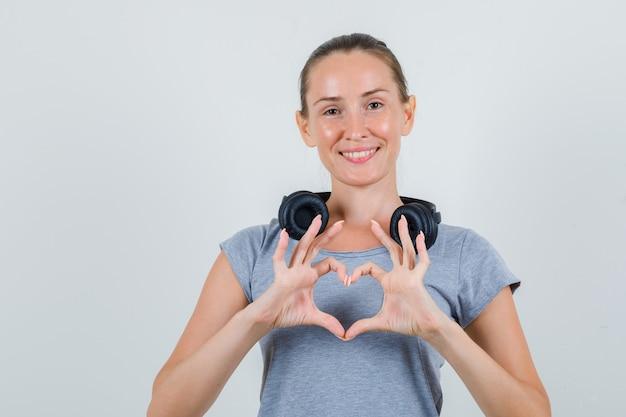 Jong wijfje dat hartvorm met vingers in grijs t-shirt maakt en vrolijk kijkt. vooraanzicht.