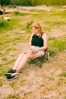 Jong wijfje dat laptop in bos met behulp van