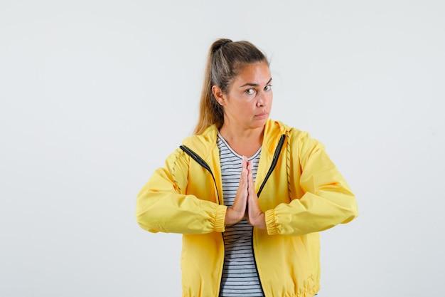 Jong wijfje dat namaste-gebaar in jasje, t-shirt toont en zelfverzekerd, vooraanzicht kijkt.
