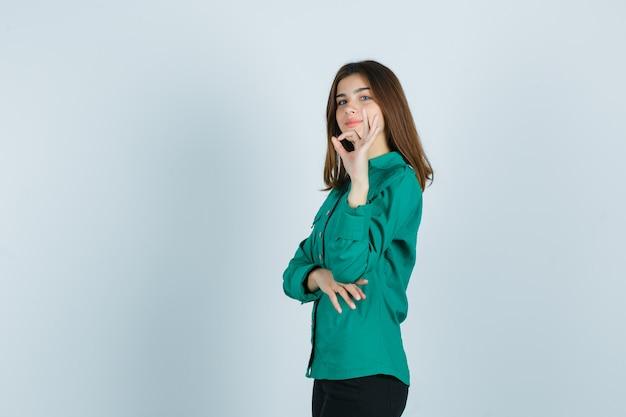 Jong wijfje dat ok gebaar in groen overhemd, broek toont en trots kijkt.