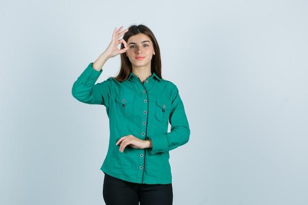 Jong wijfje dat ok gebaar in groen overhemd toont en vrolijk, vooraanzicht kijkt.