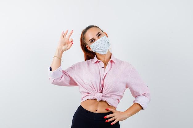 Jong wijfje dat ok gebaar toont terwijl hand op heup in overhemd, broek, medisch masker wordt gehouden en er zelfverzekerd uitziet. vooraanzicht.