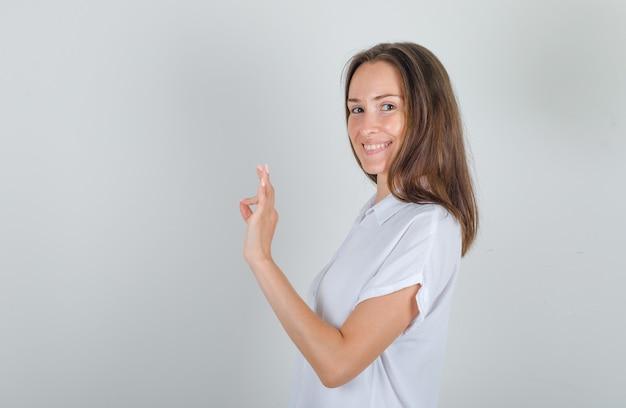 Jong wijfje dat ok teken in wit overhemd doet en tevreden kijkt.