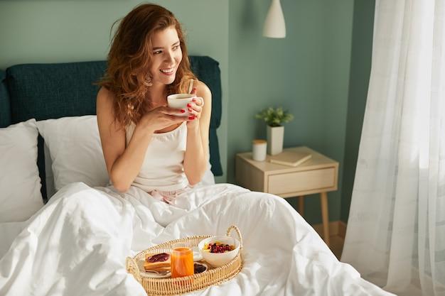 Jong wijfje dat ontbijt op bed heeft