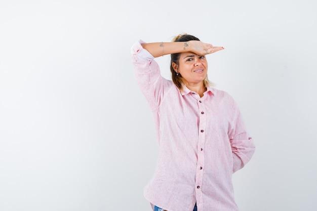 Jong wijfje dat opgeheven hand op hoofd in roze overhemd houdt en vrolijk kijkt