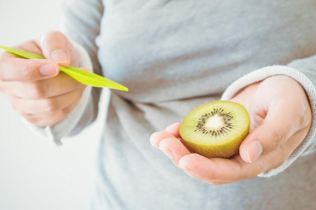Jong wijfje dat rijp kiwifruit met houten lepel eet