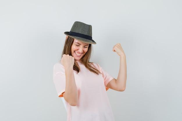 Jong wijfje dat winnaargebaar in roze t-shirt, hoed toont en gelukkig kijkt. vooraanzicht.
