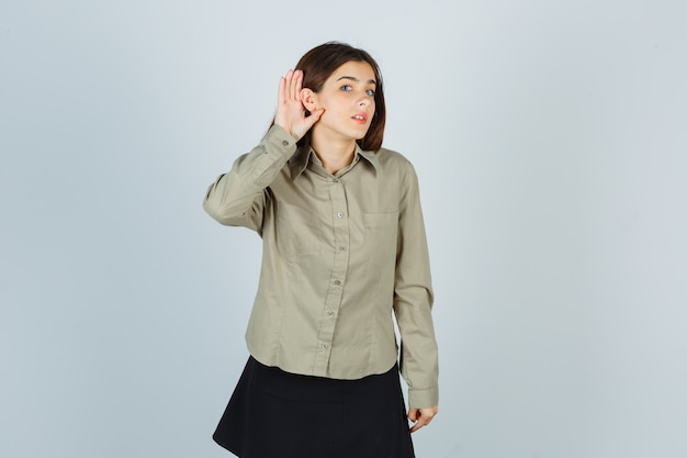 Jong wijfje die hand achter oor in overhemd, rok houden en nieuwsgierig kijken