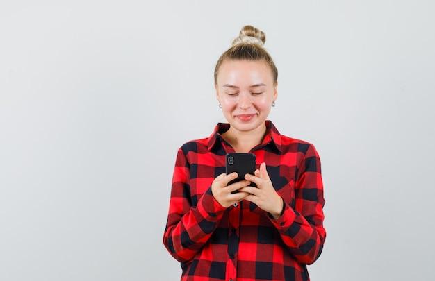 Jong wijfje die mobiele telefoon in ingecheckte overhemd gebruiken en vrolijk kijken. vooraanzicht.