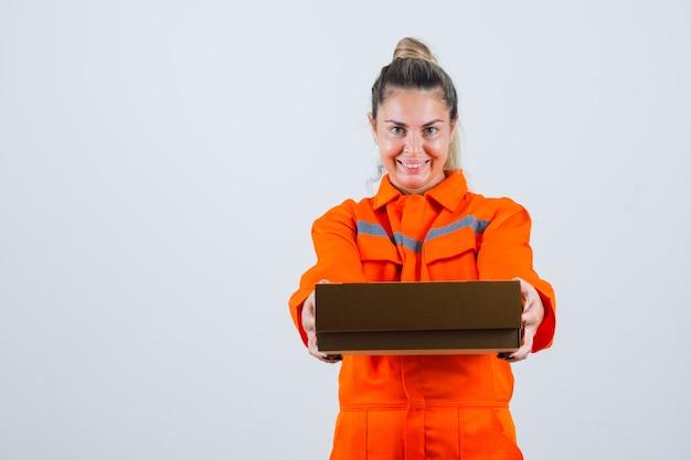 Jong wijfje in arbeidersuniform die lege doos tonen en optimistisch, vooraanzicht kijken.