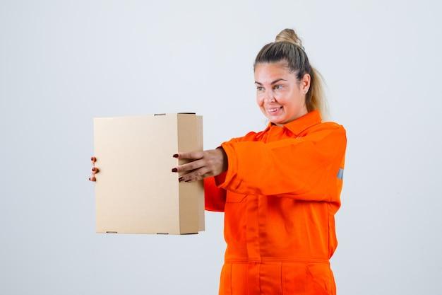 Jong wijfje in arbeidersuniform die vierkante doos toont en tevreden, vooraanzicht kijkt.