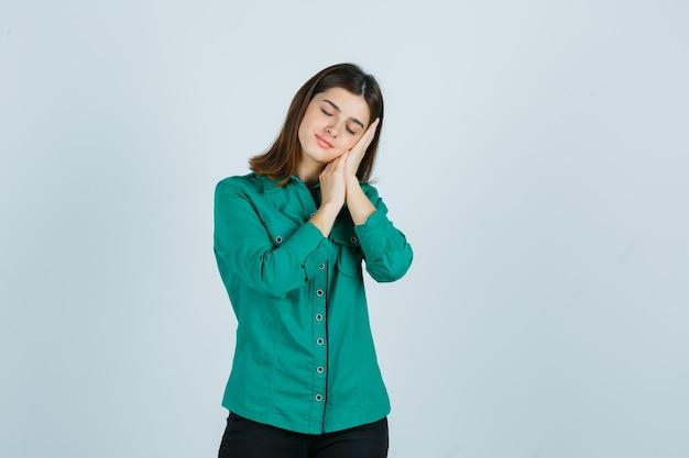 Jong wijfje in groen overhemd dat op handpalmen als hoofdkussen leunt en vreedzaam, vooraanzicht kijkt.