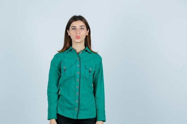 Jong wijfje in groen overhemd die lippen pruilen en leuk, vooraanzicht kijken.
