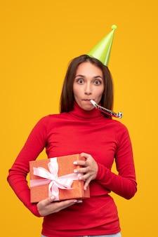 Jong wijfje in rode coltrui en partij glb die giftdoos draagt en noisemaker blaast tijdens verjaardagsviering tegen gele achtergrond