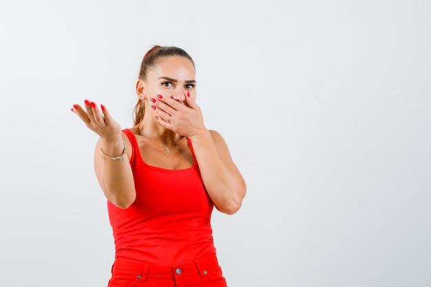 Jong wijfje in rood mouwloos onderhemd, broek die iets toont terwijl hand op mond wordt gehouden en verbaasd, vooraanzicht kijkt.