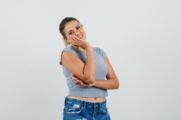 Jong wijfje in t-shirt, korte broek die hand op wang houdt en mooi kijkt