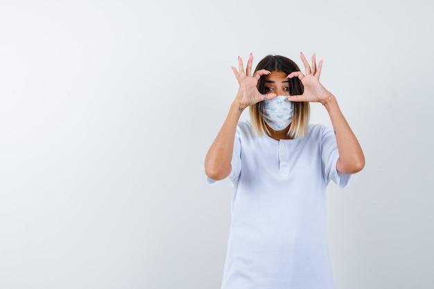 Jong wijfje in t-shirt, masker dat glazengebaar toont en leuk, vooraanzicht kijkt.