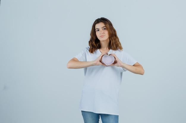 Jong wijfje in wit t-shirt, jeans die giftdoos houden en op zoek zelfverzekerd, vooraanzicht.