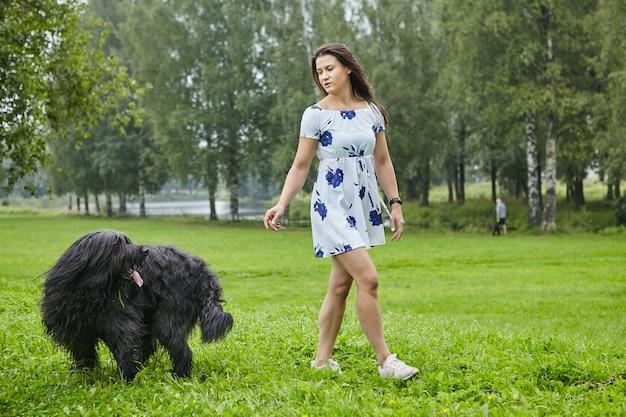 Jong wit meisje in jurk loopt overdag met zwarte ruige hond in openbaar park.