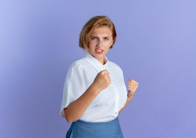 Jong woedend blond russisch meisje houdt vuisten klaar om te slaan geïsoleerd op paarse achtergrond met kopie ruimte Gratis Foto