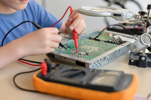 Jong wonderkind diagnosticeert en repareert kapotte printplaat met multimeter