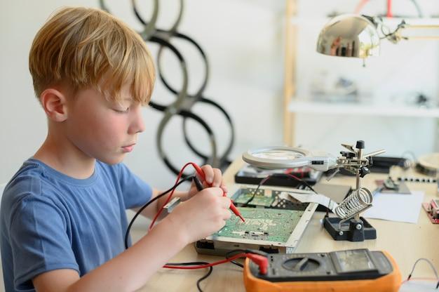 Jong wonderkind jaar oud kind diagnosticeren en repareren van printplaat met multimeter thuis