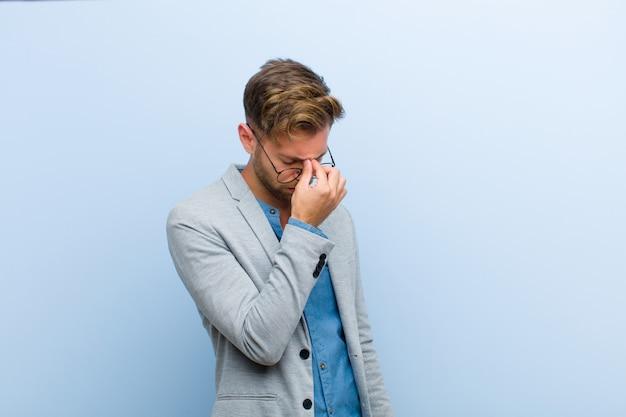 Jong zakenman beklemtoond, ongelukkig en gefrustreerd gevoel, wat betreft voorhoofd en het lijden aan migraine van ernstige hoofdpijn tegen blauwe achtergrond