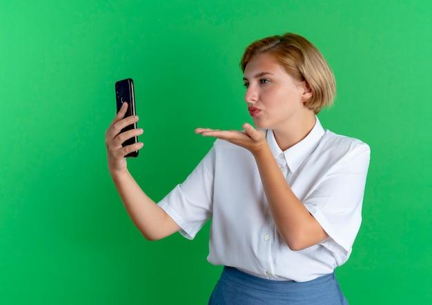 Jong zelfverzekerd blond russisch meisje houdt en stuurt een kus met de hand naar de telefoon
