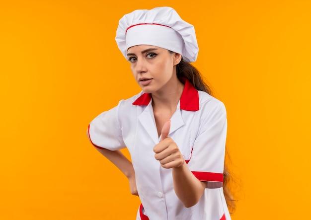 Jong zelfverzekerd kaukasisch kokmeisje in eenvormige chef-kok duimen omhoog en legt hand op taille die op oranje muur met exemplaarruimte wordt geïsoleerd