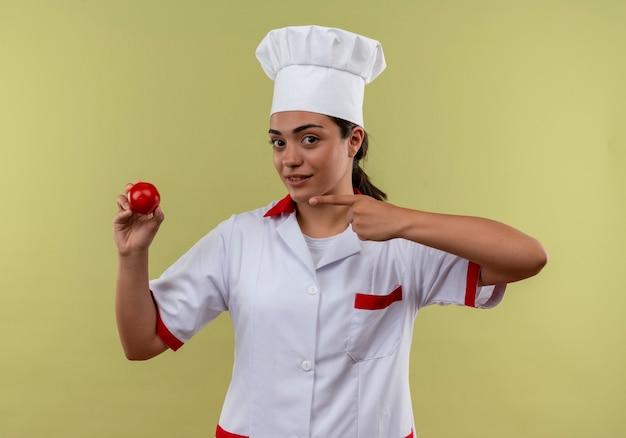 Jong zelfverzekerd kaukasisch kokmeisje in eenvormige chef-kok houdt en wijst naar tomaat geïsoleerd op groene muur met kopie ruimte