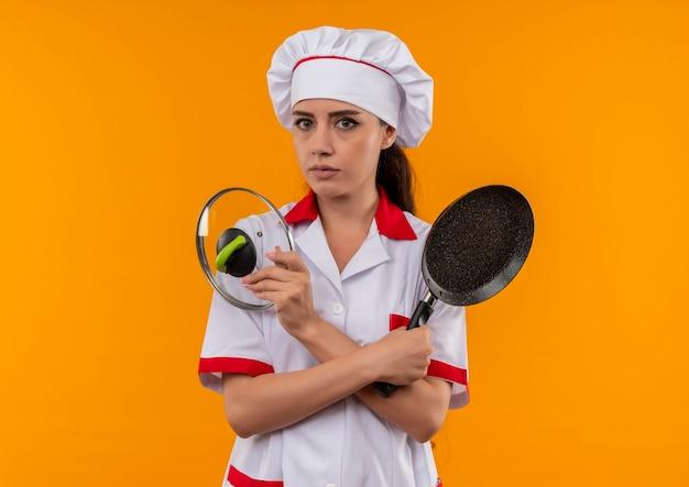 Jong zelfverzekerd kaukasisch kokmeisje in eenvormige chef-kok houdt koekenpan en deksel geïsoleerd op oranje muur met kopie ruimte