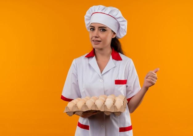 Jong zelfverzekerd kaukasisch kokmeisje in eenvormige chef-kok houdt partij eieren en duimen omhoog geïsoleerd op oranje muur met exemplaarruimte