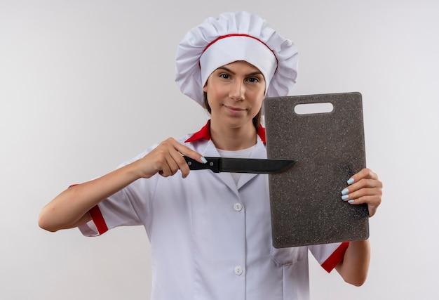 Jong zelfverzekerd kaukasisch kokmeisje in eenvormige chef-kok houdt snijplank en mes geïsoleerd op een witte achtergrond met kopie ruimte