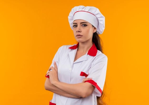 Jong zelfverzekerd kaukasisch kokmeisje in eenvormige chef-kok kruist wapens die op oranje muur met exemplaarruimte worden geïsoleerd