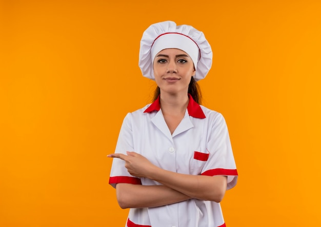 Jong zelfverzekerd kaukasisch kokmeisje in eenvormige chef-kok kruist wapens en wijst naar de kant die op oranje muur met exemplaarruimte wordt geïsoleerd