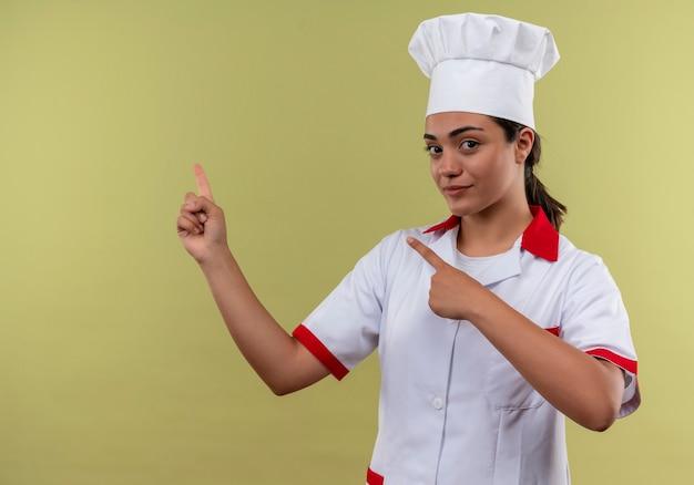 Jong zelfverzekerd kaukasisch kokmeisje in eenvormige chef-kok wijst naar de kant die op groene muur met exemplaarruimte wordt geïsoleerd